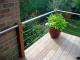 decking balustrade with stainless steel tubular handrail and cable infill